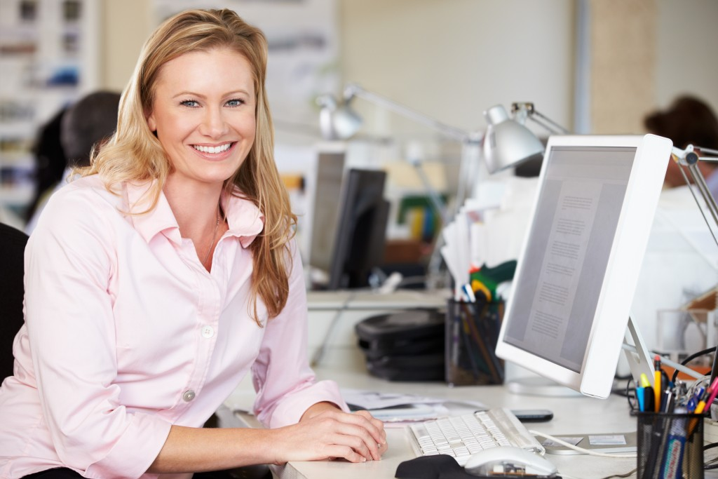 bigstock-Woman-Working-At-Desk-In-Busy--43130395